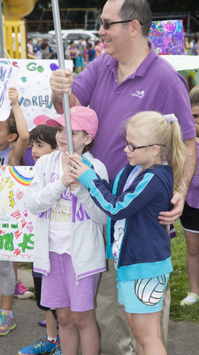 Seraphina O'Brien (left) is joined by her father and sister at the finish line for the Manorhaven School's Walk to Fitness. The walk was made possible through the Kohl's Cares Keeping Kids Healthy Program.